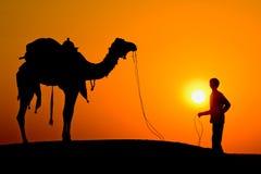 Силуэт человека и верблюда на заходе солнца в пустыне, Jaisalmer - Индии Стоковые Фото
