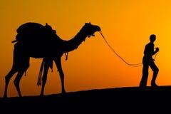 Силуэт человека и верблюда на заходе солнца в пустыне, Jaisalmer - Индии Стоковая Фотография