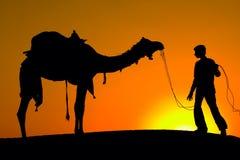 Силуэт человека и верблюда на заходе солнца в пустыне, Jaisalmer - Индии Стоковая Фотография RF