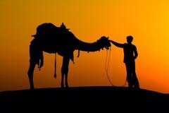 Силуэт человека и верблюда на заходе солнца, Jaisalmer - Индии Стоковое фото RF