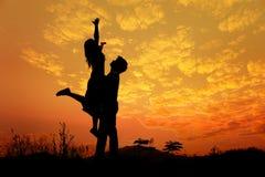 Силуэт человека и женщина любят в заходе солнца Стоковые Изображения RF