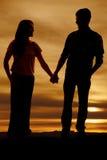 Силуэт человека и женщины держа руки Стоковое фото RF