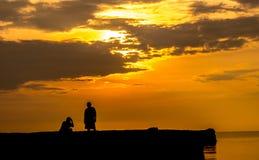 Силуэт человека и женщин с предпосылкой захода солнца Стоковое Изображение RF