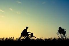 Силуэт человека и старого велосипеда на траве Стоковое фото RF