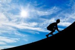 Силуэт человека карабкаясь вверх Стоковые Изображения