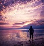 Силуэт человека наслаждаясь заходом солнца на море Стоковое фото RF