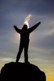 Силуэт человека на горе во время захода солнца зимы Стоковое фото RF