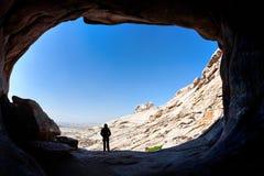Силуэт человека перед входом пещеры стоковые фото