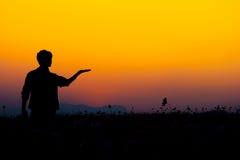 Силуэт человека представляя на заходе солнца Стоковое Фото