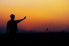 Силуэт человека представляя на небе захода солнца Стоковое Изображение RF