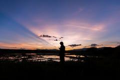 Силуэт человека стоя в ниве на заходе солнца Стоковые Изображения