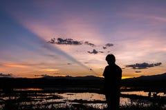 Силуэт человека стоя в ниве на заходе солнца Стоковые Фото