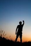 Силуэт человека стоя в поле Стоковые Изображения RF