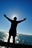 Силуэт человека стоя на пристани, раскосный обрамлять стоковое фото