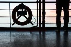 Силуэт человека стоя около кольца жизни Стоковое Фото