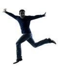 Силуэт человека счастливый скача салютуя во всю длину Стоковые Фото