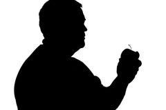 Силуэт человека с избыточным весом с яблоком в его руке Стоковые Фотографии RF