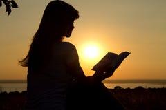 Силуэт чтения девушки на заходе солнца Стоковая Фотография RF