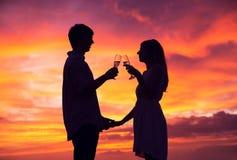 Силуэт шампанского пар выпивая на заходе солнца Стоковое Фото