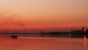 Силуэт шлюпки в реке на twilight времени стоковое фото rf
