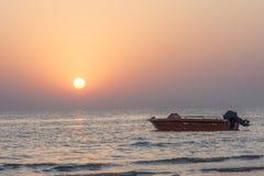 Силуэт шлюпки скорости с заходом солнца Стоковая Фотография RF