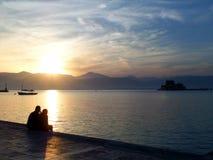 Силуэт любовников наблюдая заход солнца на портовом районе в Греции Стоковые Фотографии RF