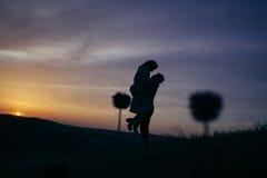 Силуэт любящей пары целуя в заходе солнца Стоковая Фотография RF