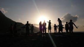 Силуэт людей делая время восхода солнца побережья йоги на море Стоковые Изображения