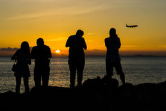 Силуэт людей и самолета во время захода солнца Стоковое фото RF