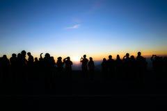 Силуэт людей и туриста во время красивой горы su Стоковые Изображения