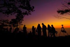 Силуэт людей принимая фото восхода солнца стоковое фото