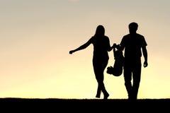 Силуэт людей семьи из трех человек идя на заход солнца Стоковое фото RF