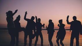 Силуэт людей танцев группы молодых имеет партию на пляже на заходе солнца сток-видео