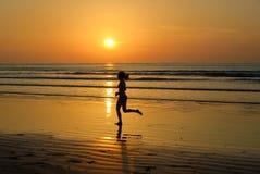 Силуэт jogger женщины бежать на пляже захода солнца Стоковые Изображения