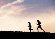 Силуэт jogging человека и женщины бежать совместно в заход солнца Стоковые Изображения