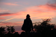 Силуэт ` s девушки на заходе солнца Стоковая Фотография