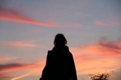 Силуэт ` s девушки на заходе солнца Стоковые Изображения RF