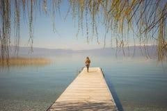 Силуэт ` s женщины стоя на пристани озера Стоковая Фотография