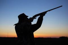Силуэт ` s охотника на заходе солнца Стоковое Изображение RF
