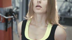 Сильная девушка разрабатывая с гантелью для бицепса в 4K видеоматериал