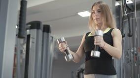 Сильная девушка разрабатывая с гантелью для перепада muscles в 4K сток-видео