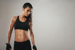 Сильная женщина в черных атлетических стойках одежд Стоковые Изображения RF
