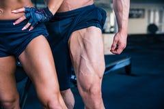 Сильная женщина и мышечный человек представляя на спортзале Стоковая Фотография