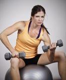 Сильная красивая женщина поднимая свободные весы Стоковое фото RF