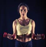 Сильная молодая женщина делая скручиваемости бицепса Стоковое Изображение