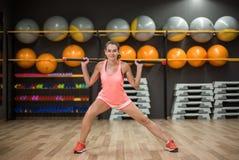 Сильная тренировка девушки с ручкой фитнеса Женщина в розовых sporty одеждах на запачканной предпосылке спортзала релаксация pila Стоковое Изображение RF