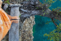 Сильно детальные ноги женщины фото Девушка смотря вниз с дерева скалы старого Голубой предпосылка океана запачканная водой горизо Стоковое Фото