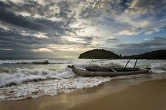 Сильные волны ударили старые деревянные шлюпку и воду брызгая вокруг шлюпки стоковые фото