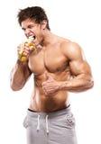 Сильный атлетический человек показывая мышечное тело и есть банан стоковая фотография rf