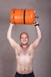Сильный без рубашки человек поднимая газовый баллон Стоковое Изображение RF